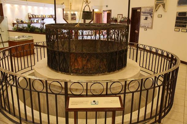 Historic Zamzam well mouthpiece. The description reads: (line 1) The mouthpiece of the well of Zamzam. (line 2) The pulley for lifting Zamzam water dating back to the end of the fourteenth century of Hijrah. (line 3) The brass bucket which was used to be in the well of Zamzam dating back to 1299 Hijrah. (Mohammad Bahareth/CC BY SA 2.0)