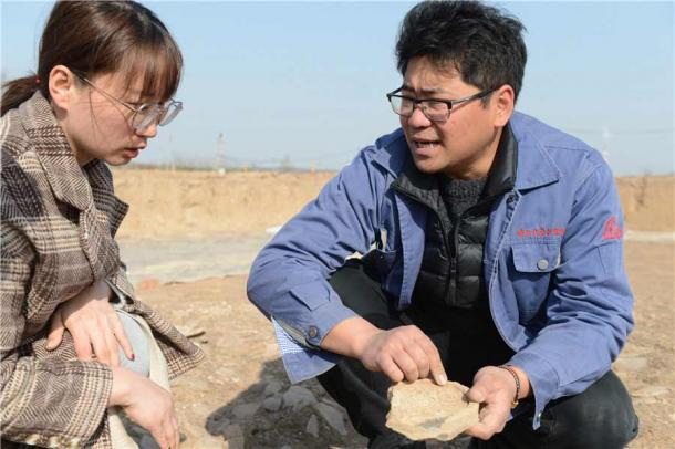 Zhang Yanglizheng, from the Shaanxi Academy of Archaeology, right, and a worker from the local relic's bureau, examine a tile found in the ruins. (Zhang Xiping / China Daily)
