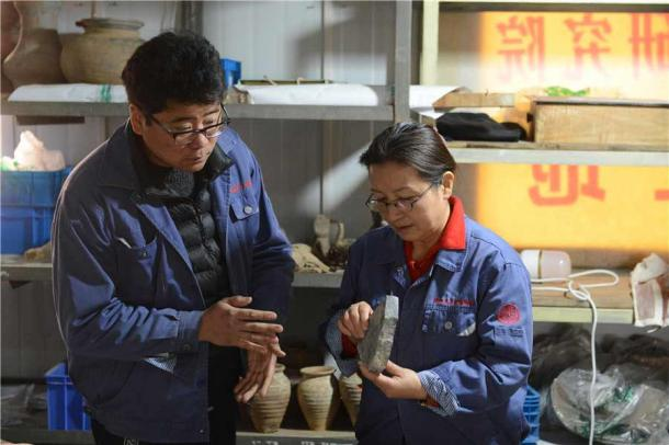 Zhang Yanglizheng and Xu Weihong, a researcher from the academy and leader of the team, study relics found at the ancient Xianyang site. (Zhang Xiping / China Daily)