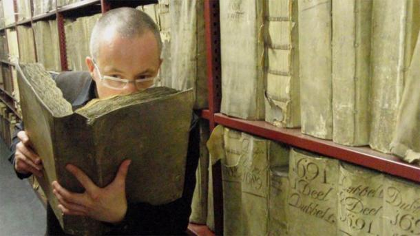 An AI robot will be used to scan historic texts and paintings as parte of the Odeuropa project, which aims to create a smell encyclopedia and recreate smells of the past. In the image Professor Matija Strlic smells an ancient text in the National Archives of The Netherlands. (Matija Strlic / Odeuropa)