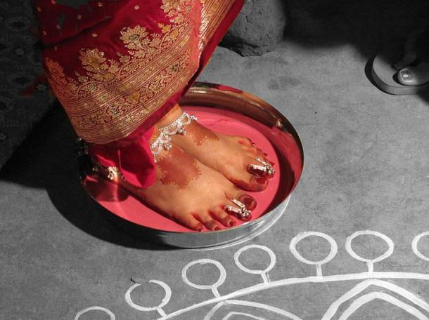 An ancient Indian tradition: the ceremony welcoming the newly wed bride, wearing toe rings, to her new home, with her feet dipped in a mixture of milk and alta (lac dye).