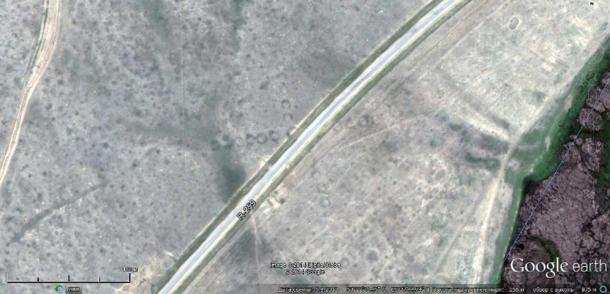 Satellite image showing the road R-259 bisecting an ancient Torgay geoglyph in Kazakhstan.