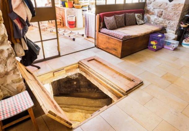 The ancient bath is concealed beneath a pair of wooden doors in the family living room.