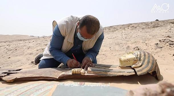 Another one of the ancient Egyptian sarcophagi unearthed at the Saqqara archaeological site, being inspected by an archaeologist. (Egypt's Ministry of Tourism and Antiquities)