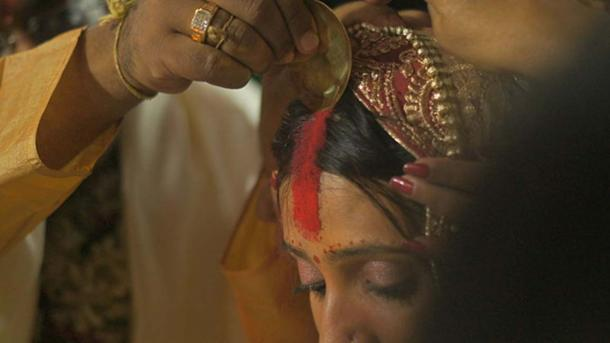 he ritual of applying the Sindoor (a traditional cosmetic powder) as part of a Hindu Indian wedding.