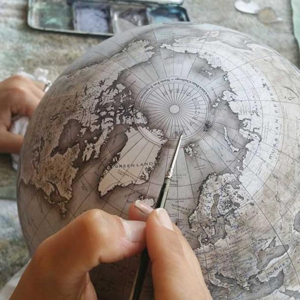 An artist painting details onto a globe.