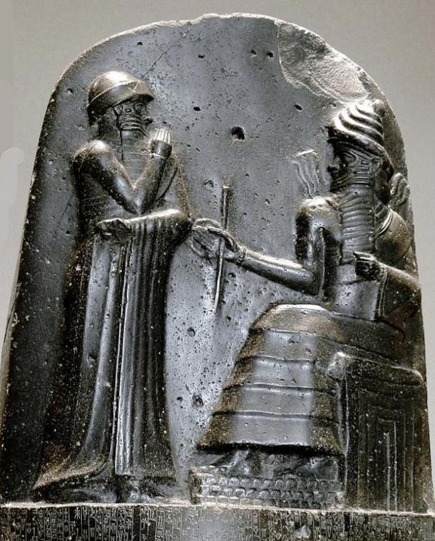 "The top of a basalt stele, ""Code of Hammurabi"". Hammurabi (standing), is depicted as receiving his royal insignia from Shamash. Hammurabi holds his hands over his mouth as a sign of prayer. Circa 1792 - 1750 BC."