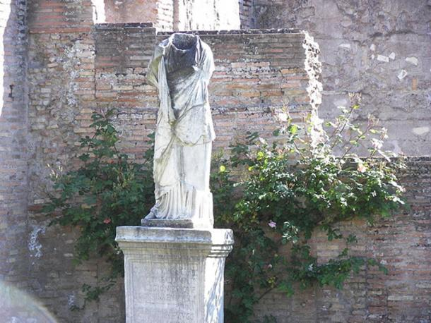 A beheaded statue at the House of the Vestals in the Forum Romanum in Rome. The name of the Vestal virgin has been erased, and only its initial, 'C' can be reconstructed.
