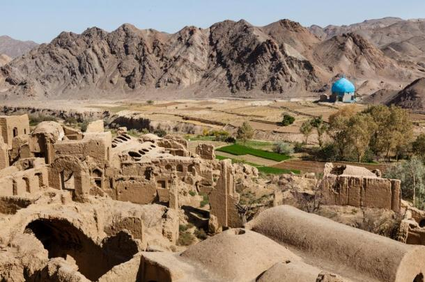 A blue-domed mosque stands out against the earthen colors of the surrounding landscape.
