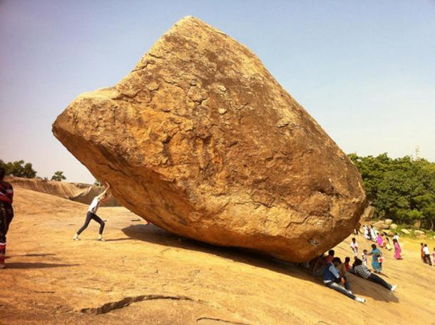 A person trying to move the boulder