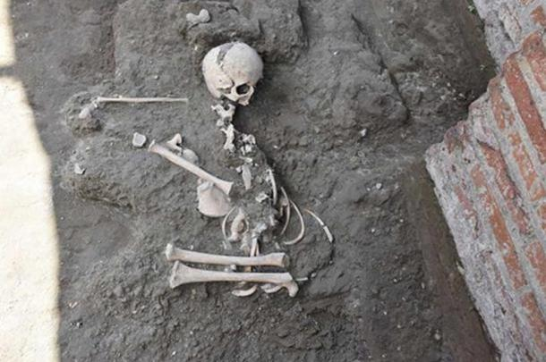 The child's skeleton was found in a crouching position in the bath complex of the town.