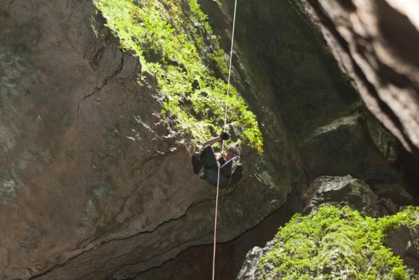 Chris rappelling down into the cave