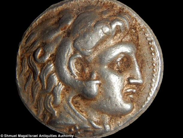 A coin depicting Alexander the Great on one side. The image of Zeus on a throne is said to be portrayed on the other side. Minted coins help experts date finds.
