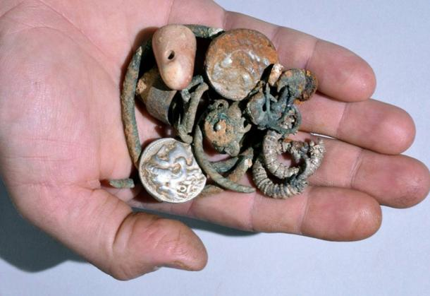 Coins, rings, bracelets, earrings, and a stone weight; the ancient items, thought to date to the reign of Alexander the Great, were found within a cloth pouch.