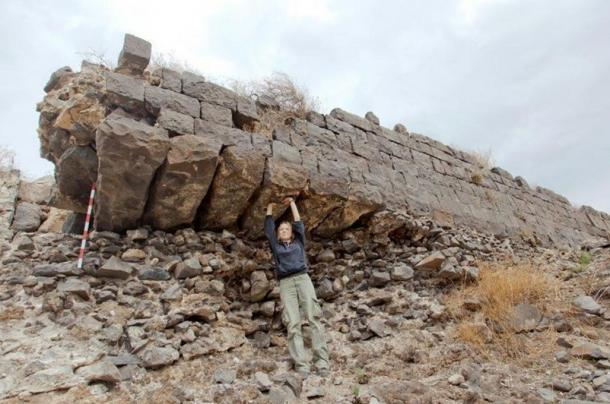 A corner of the defensive bastion over the southern cliff; Y. Vitkalov of the excavation team pretends to support the basalt beam foundations exposed after mortar washed away.
