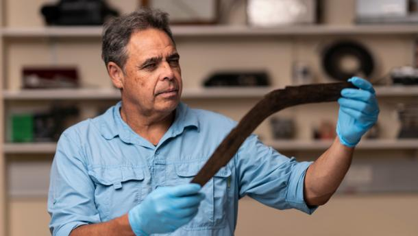 Dave Johnston, Professor of Archaeology from the Australian National University analyzing one of sixe boomerangs discovered recently in Australia. (Jamie Kidston /Australian National University)