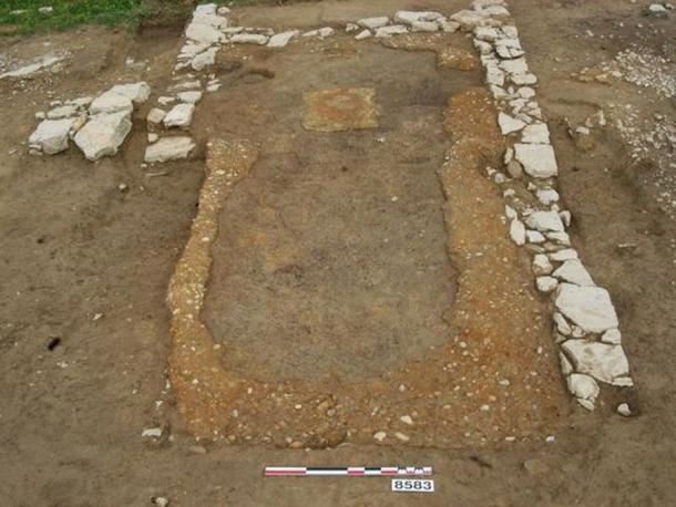 The dining room of the ancient tavern, showing banks of pebbles where built-in benches once stood against the walls.