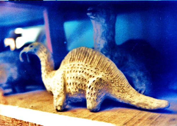 What appears to be a dinosaur sculpture in the collection of strange artifacts.