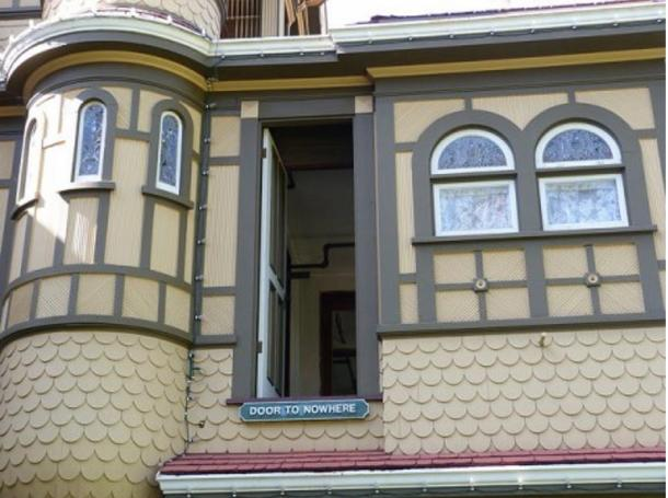 """A door in the Winchester Mystery House opening out onto a three-story drop, now labelled """"Door to Nowhere."""""""