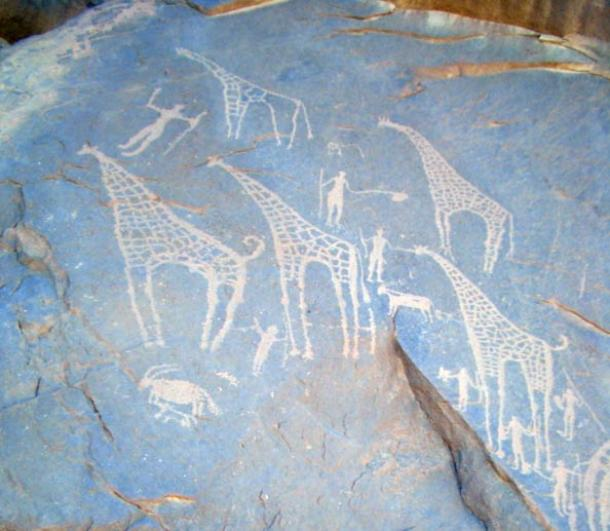 Giraffes and what look like a goat, a dog, people and cows on cave walls in the Egyptian Sahara