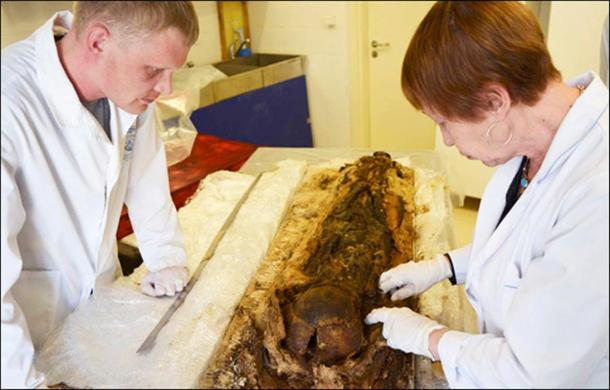 The boy's remains are seen as being accidentally preserved aided by the form of burial in a cocoon of birch bark and copper.