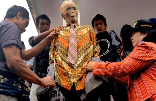 A family dresses up the corpse of a family member in new clothes