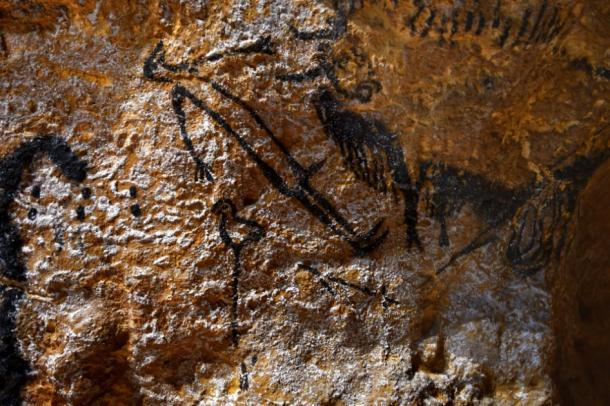 The famous shaft scene of Lascaux Cave, a man with a bird head and a bison. (bobdu11 / Adobe Stock)