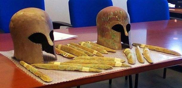 Some of the orichalcum ingots and the two Corinthian helmets found near a 2,600-year-old shipwreck off the coast of Sicily.
