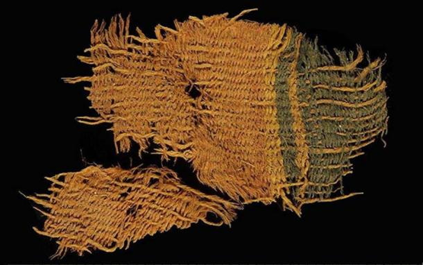 A fine wool textile dyed red and blue, found at Timna. The textile used the various colors of natural animal hair to create black and orange-brown colors for decorative bands.