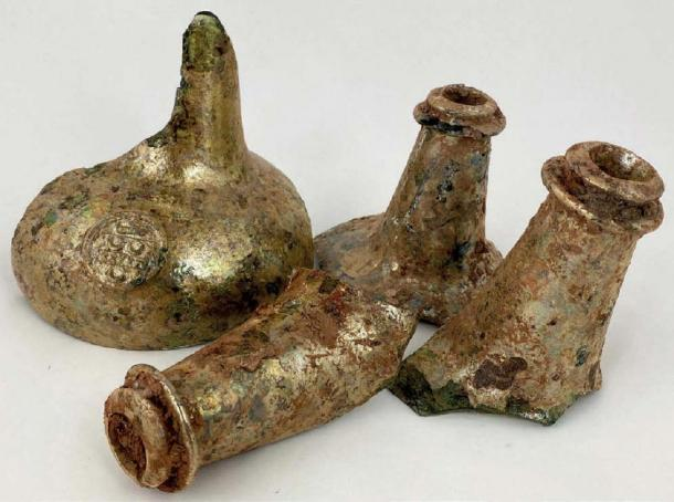 This group of four neck fragments, including one with a seal, found with wine bottles. (©BBR Auctions)