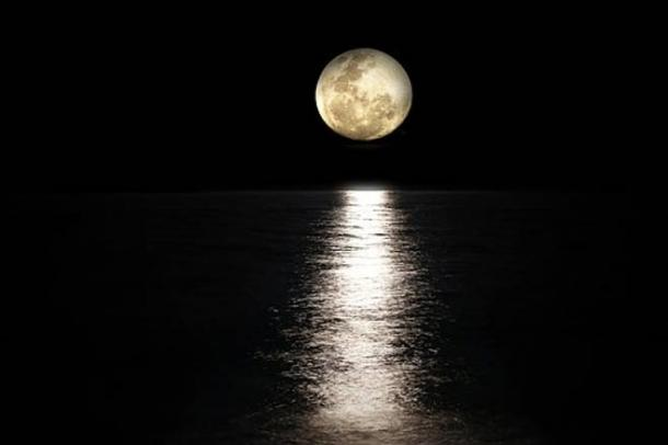 A full moon over water.