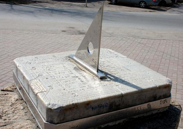 The gnomon is the triangular blade in this sundial.