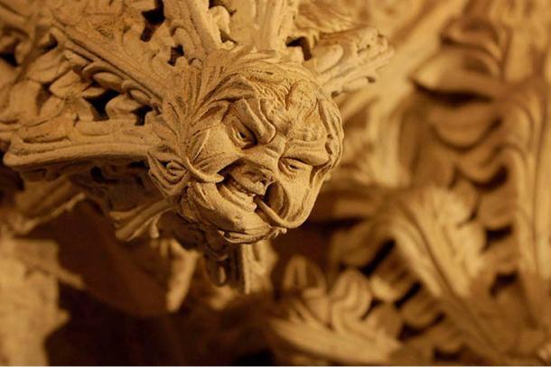The 'Green Man' of the Rosslyn Chapel is depicted with vines coming out of his mouth and surrounded by foliage.
