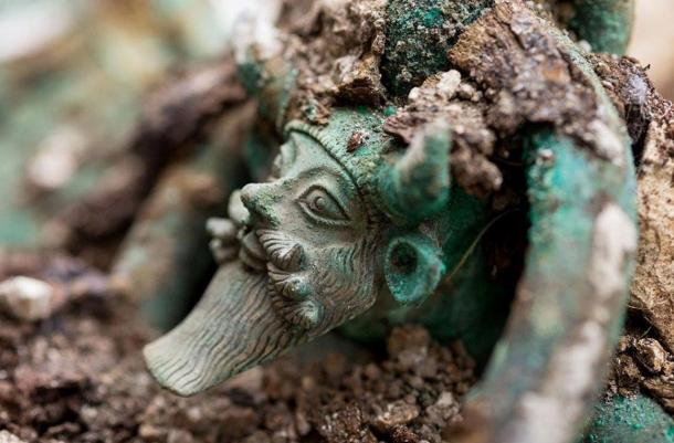 The handles of a large cauldron in the tomb are decorated with the Greek river God Achelous