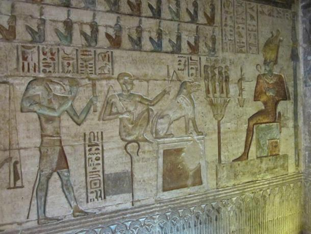 Thoth, left, on a relief depicting the weighing of the heart ritual in the afterlife, with Osiris seated on the right. Deir el-Medina