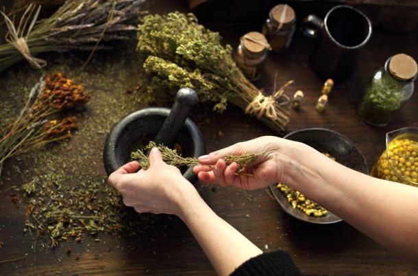 An herbalist at work grinding up and mixing medicinal herbs