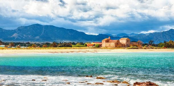 The Nora bay and beach, the medieval Sant'Efisio church near the shore and mountains in the background (pilat666 / Adobe Stock)