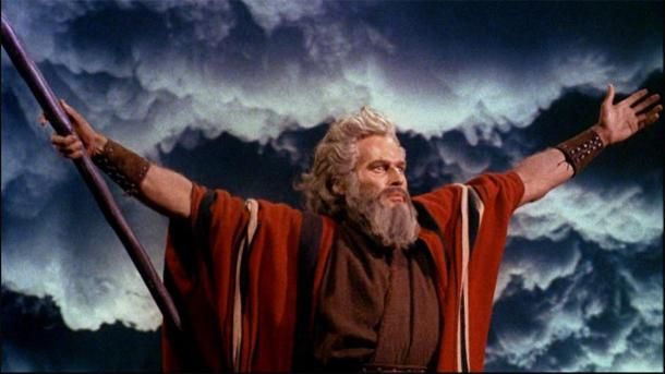 Charlton Heston as Moses in 'The Ten Commandments' (1956), raising his arms as he separates the waters of the Red Sea in a classic pose of Egyptian magicians and priests. (Public Domain)