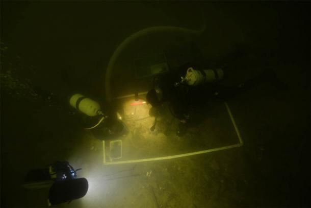 Underwater archaeologists examining the artifacts in Lake Asveja, Lithuania. (G. Krakauskas)
