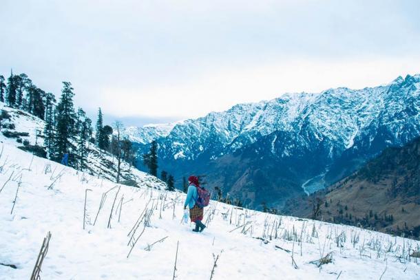 Woman walking through the Kashmir winter landscape. (gajendra / Adobe Stock)