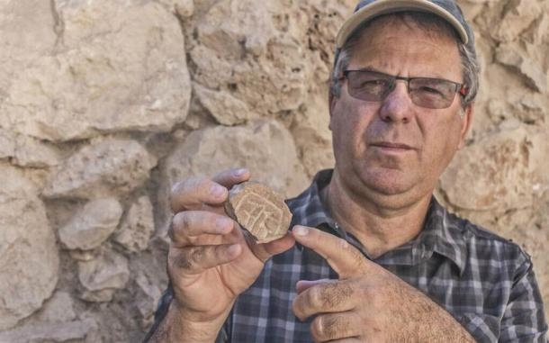 Prof. Yuval Gadot, from Tel Aviv University, poses with Persian-era seal discovered in the excavation of a parking lot in Jerusalem. (Shai Halevy / Israel Antiquities Authority)