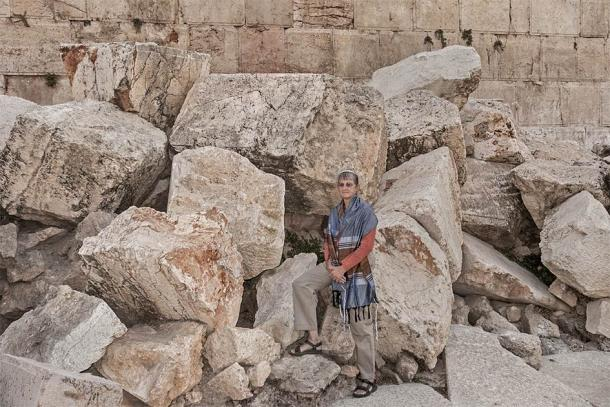 """A female rabbi posing on the massive stones thrown down from the Temple Mount by the Romans during the Great Jewish Revolt in Jerusalem where the """"cursed"""" ballista stones were taken from. (Sarit Richerson / Adobe Stock)"""
