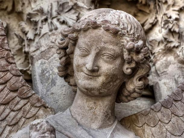 A smiling angel, yet so humanlike, that was carved in stone at the Reims Cathedral, France. Could this also be a medieval self portrait of the master stonemason who made this work? (Jorge Alves / Adobe Stock)
