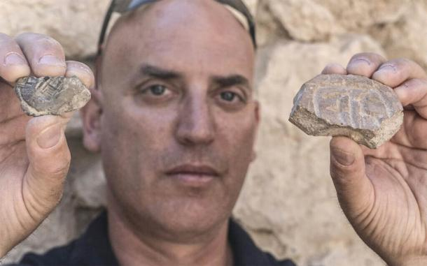 Dr. Yiftah Shalev, from the Israel Antiquities Authority, with the Persian-era seal and seal impression, both discovered in the excavation of a parking lot in Jerusalem. (Shai Halevy / Israel Antiquities Authority)