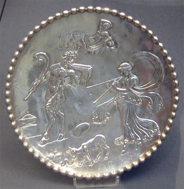 One of a pair of silver dishes from the Mildenhall Treasure; decorated with figures of Pan, a nymph and other mythological creatures, all in relief; ring foot on underside; inscribed 'EVATTPLOY' on the base. (British Museum / CC0)