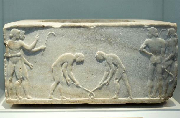 Base of a funerary kouros, found in Kerameikos, built into Themistokleian wall. Decorated with what appear to be players of a game similar to hockey. (Zde / CC BY-SA 3.0)