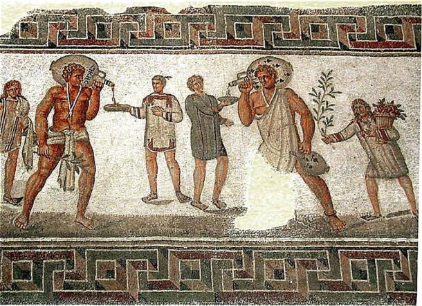 Roman mosaic from Dougga, Tunisia (2nd century AD): the two slaves carrying wine jars wear typical slave clothing and an amulet against the evil eye on a necklace; the slave boy to the left carries water and towels, and the one on the right a bough and a basket of flowers. (Pascal Radigue/CC BY 3.0)