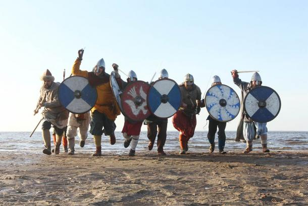 Representation of warriors running into battle using Viking weapons and the typical round shield. (destillat / Adobe stock)