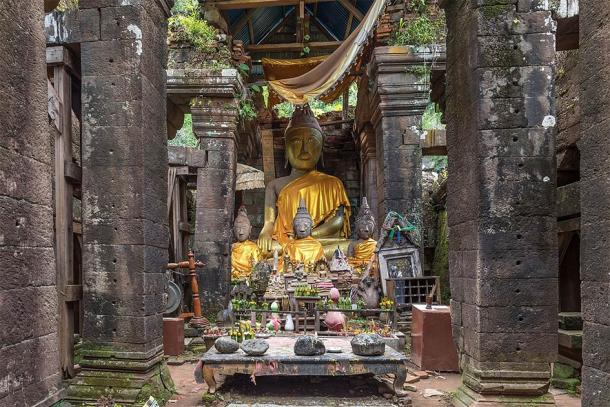 Clothed statues of the Buddha seated, table with stones and Buddhist relics, at the center of Vat Phou Temple. (Basile Morin / CC BY-SA 4.0)