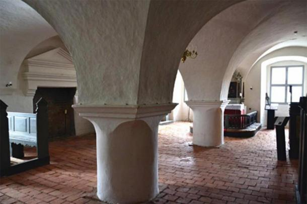 The chapel with brick vaults and the fireplace to the left. The borderline between the circular higher half and the plain, straight lower half is clearly emphasized, having yin-yang-like opposite joints where columns meet vaults. (Author provided)